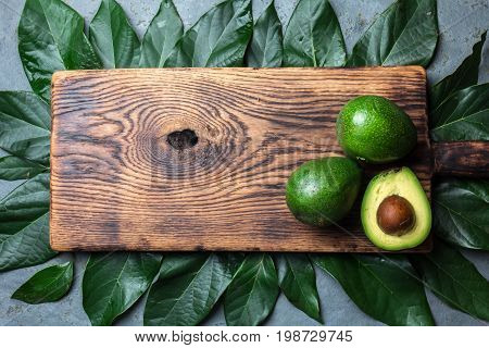 Food Background With Fresh Avocado, Avocado Tree Leaves And Wooden Cutting Board. Harvest Concept, G