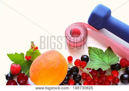 Ripe red currant black currant raspberries and cherry on a white background. Dumbbells healthy lifestyle fitness. Berries on the border of the image with a copy of the space for text.
