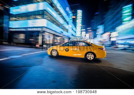 Nyc Yellow Cab Passing Fast At Night In Timesquare Manhattan, New York.