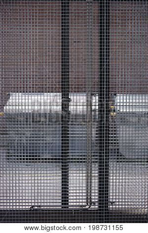 Waste containers are behind a grid fence in a lockable outdoor area.