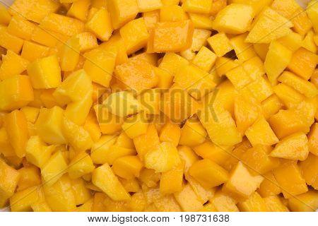 Chopped mango. Orange juicy fruit background. Sliced mango flesh