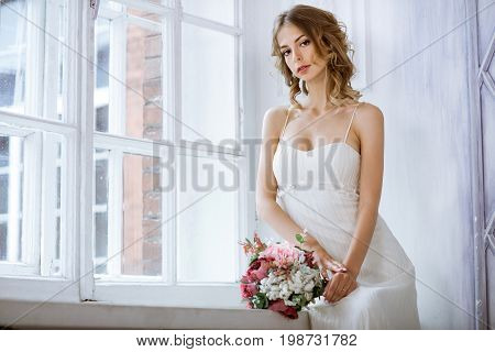 Brunette bride in fashion white wedding dress with makeup. Wedding day of bride in bridal gown. Beauty woman and bouquet. Fashion brunette model indoors. Beauty portrait of model in white bridal dress