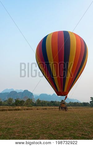 VANG VIENG LAOS - MARCH 15 2017: Vertical picture of a striped balloon landing in Vang Vieng Laos.
