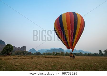 VANG VIENG LAOS - MARCH 15 2017: wide angle picture of a striped balloon landing in Vang Vieng Laos.
