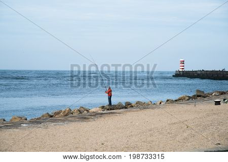 Man Fishing Infront Of Lighthouse