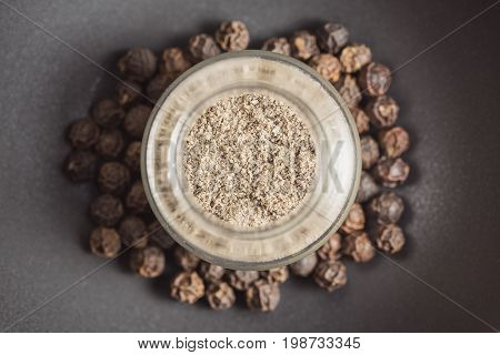 Ground black pepper in a glass jar and peppercorns in the dark black background. Top view with symmetrical center composition
