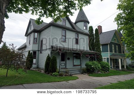 CADILLAC, MICHIGAN / UNITED STATES - MAY 31, 2017: A gray Victorian mansion, with a wraparound porch and a turret, and very tall sculpted arborvitae (Thuja occidentalis) plants, in the Courthouse Hill Historic District of Cadillac, Michigan.