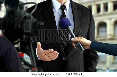 Close up of press interview with a man in black suit