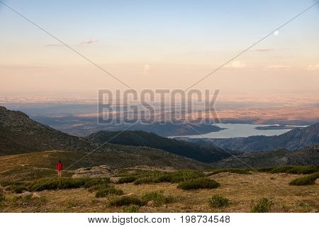 Girl climber contemplates from the top of the mountain a amazing sunset and the moonrise. Navacerrada Spain.