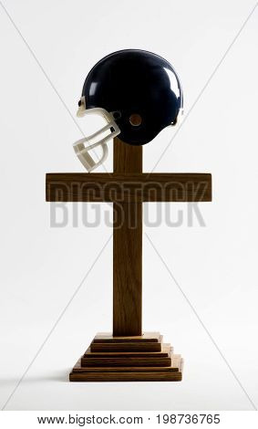 Football and the church concept with a wooden cross and helmet.