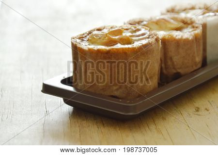 little batter cupcake paper wrapped topping custard cream and chew nut on plastic tray