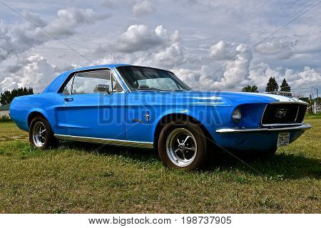 BATTLE LAKE, MINNESOTA, August 5, 2017: The blue 1966 Ford mustang is a product of the Ford Motor Company located in Dearborn, Michigan started by Henry Ford and incorporated on June 16, 1903.