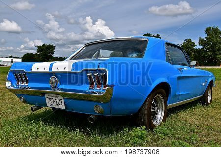 BATTLE LAKE, MINNESOTA, August 5, 2017: The blue1966 Ford mustang is a product of the Ford Motor Company located in Dearborn, Michigan started by Henry Ford and incorporated on June 16, 1903.