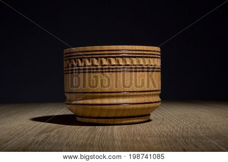 Wooden tableware for salt on a table on a black background