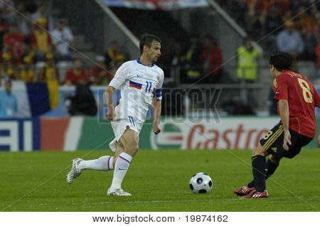 INNSBRUCK - JUNE 10: Sergei Semak of Russia (in white) & Xavi of Spain (in red)  during the match Spain-Russia 4:1 Euro2008 Group D. June 10, 2008, in Innsbruck, Austria