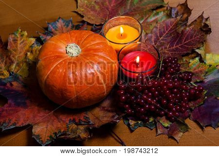 Pumpkin and candles on autumn leaves. Selective focus