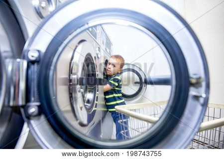 Boy puts clothes in a washing machine in a public laundry.  diligent child helps with washing in laundromat