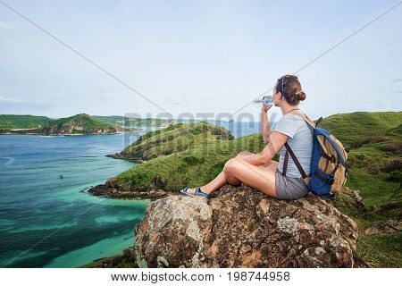 hiker on mountain with a backpack drinks water and enjoying at the beautiful coast. Hiking. Adventure and travel in the mountains coast.