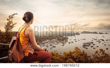 Woman traveler with backpack enjoying view coast of the bay of Cat Ba at sunset. Vietnam Traveling along mountains and coast freedom and active lifestyle concept.