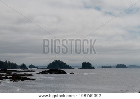 Remote Coastal View With Islands, Cliffs And Clouds