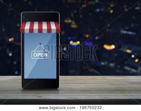 Modern smart mobile phone with on line shopping store graphic and open sign on wooden table over blur colorful night light city tower Shop online concept