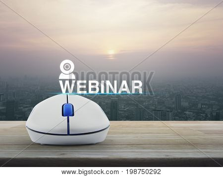 Webinar icon with wireless computer mouse on wooden table over modern city tower at sunset vintage style Seminar online concept