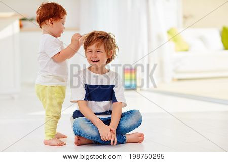 Young Kid Tolerating A Junior Brother Game With His Hair