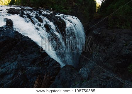 Dark waterscape scenery in forest with waterfalls