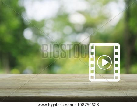 Play button with movie icon on wooden table over blur green tree Cinema online concept