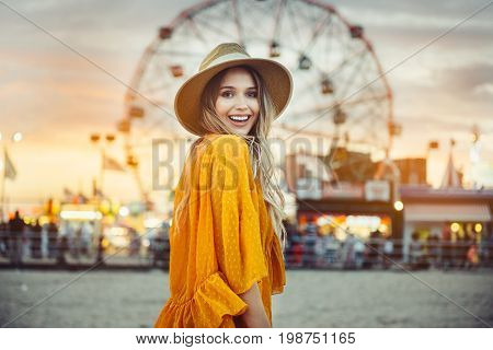 Beautiful exited smiling tourist woman having fun at amusement park at hot summer day trip on the beach.