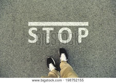 Word Stop written on an asphalt road. Top view of the legs and shoes. POV