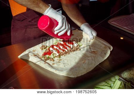 Crop person in gloves pouring ketchup in burrito while cooking in cafe.