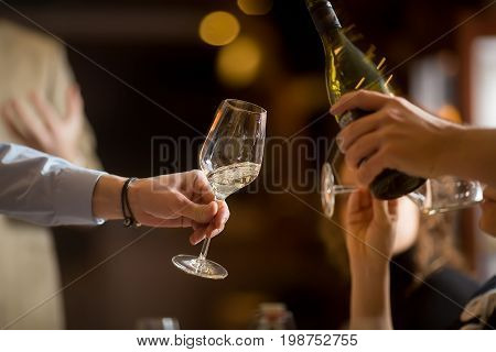 Anonymous person pouring champagne for friend in wineglass while partyin.