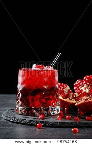 A red berry cocktail with a black straw and a part of a pomegranate on a black background. Alcoholic antioxidant beverage. A grain of bittersweet garnet.  Expensive delicacy drinks for gourmets.