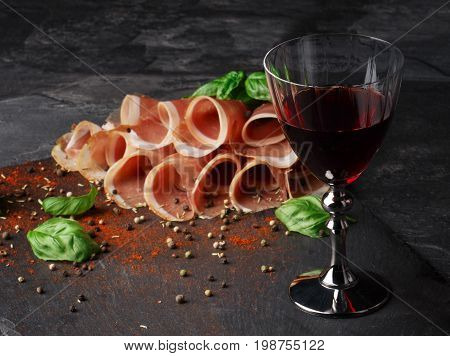 Close-up of fantastic sliced prosciutto and a glass of red wine on a black table background. Appetizing traditional  wine with meaty restaurant snacks and basil leaves. Delicatessen, luxury concept.