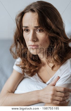 Bad mood. Portrait of an unhappy nice pleasant woman thinking about her problems and feeling unhappy while holding a pillow