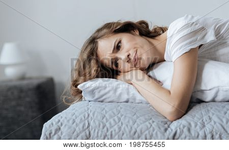 What should I do. Depressed moody young woman lying on a pillow and thinking about her future while having lots of problems