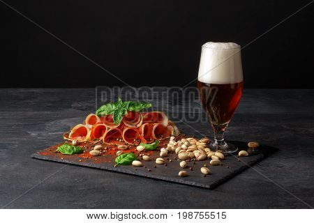 A close-up picture of a tall glass full of golden cold beer on a table. A beer with spicy snacks: salty pistachios and cut prosciutto slices on a black background. Copy space.