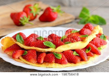 Homemade omelette stuffed with fresh strawberries on a white plate. Delicious and healthy egg omelette recipe idea. Breakfast menu. Rustic style. Closeup
