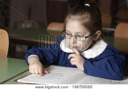 Italian elementary school girl reading on school desk. Educational and school concept