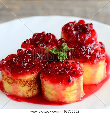 Delicious crepes rolls with red currant sauce on a white plate. Fried crepes rolls recipe. Yummy Easter breakfast idea
