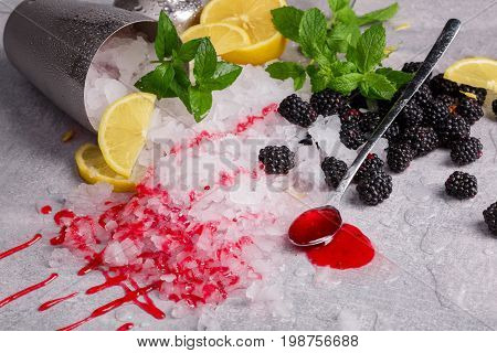 A metal bucket full of crushed ice on a gray table background. A long spoon with sweet berry syrup and fresh cold blackberries. Ice with mint twigs and cut lemons. Refreshing cocktail ingredients.