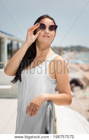 A gorgeous brunette mature lady in fantastic sunglasses on a bright beach background. A positive woman in a summer silvery silk dress. A smiling female posing on a holiday on a resort.