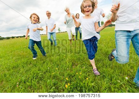 a big family are running on a green meadow