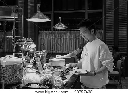 A Man Taking Food At The Buffet Restaurant