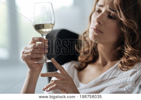 Alcoholic drink. Selective focus of a glass being filled with white wine while being held by a nice unhappy depressed woman