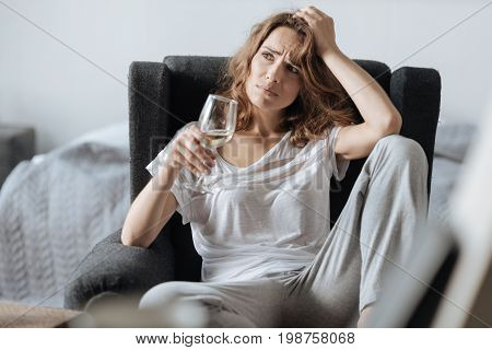 Favourite wine. Cheerless pensive nice woman holding a glass of wine and thinking about her problems while sitting in the armchair
