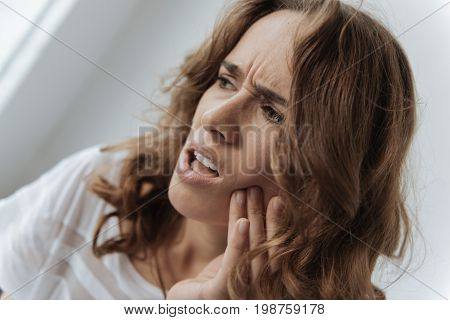 Pain in the tooth. Moody upset unhappy woman holding her cheek and thinking about visiting a dentist while having a tooth inflammation