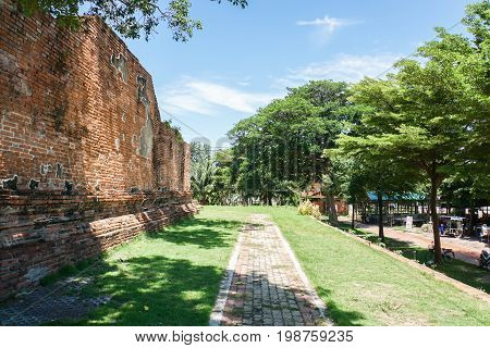 concrete walkway with green grass in historical park taken in Angthong Thailand on 30 July 2017