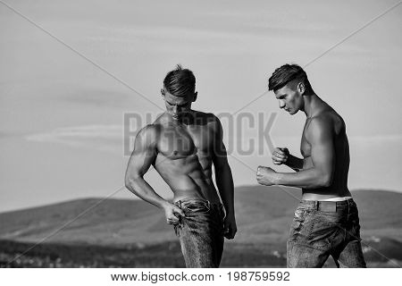 bodybuilders athletes show sexy muscular torsos with six packs abs biceps triceps outdoor in mountains on sky black and white